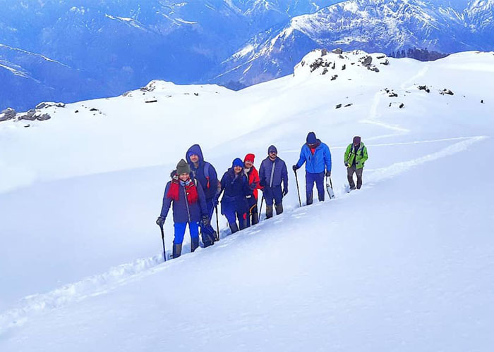 Trekkers walking on a trail towards Kedarkantha Base Camp