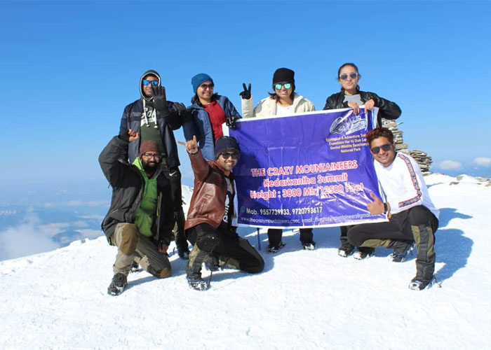 Trekkers Displaying The Crazy Mountainners Banner at Kedarkantha Summit